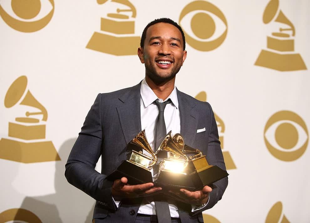 John Legend holding multiple grammys