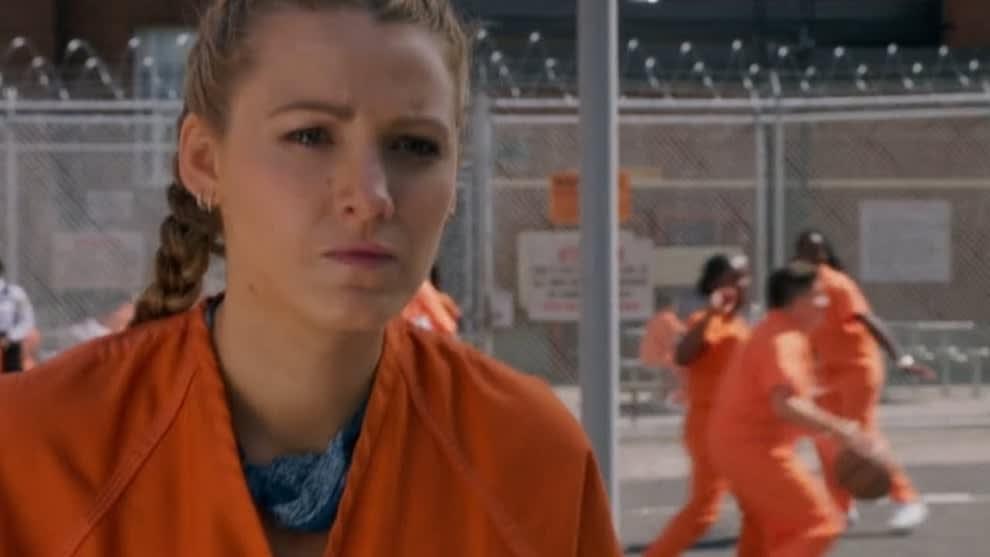 Imagem de uma personagem do filme. Ela está em uma prisão e vestindo roupas de presidiária.