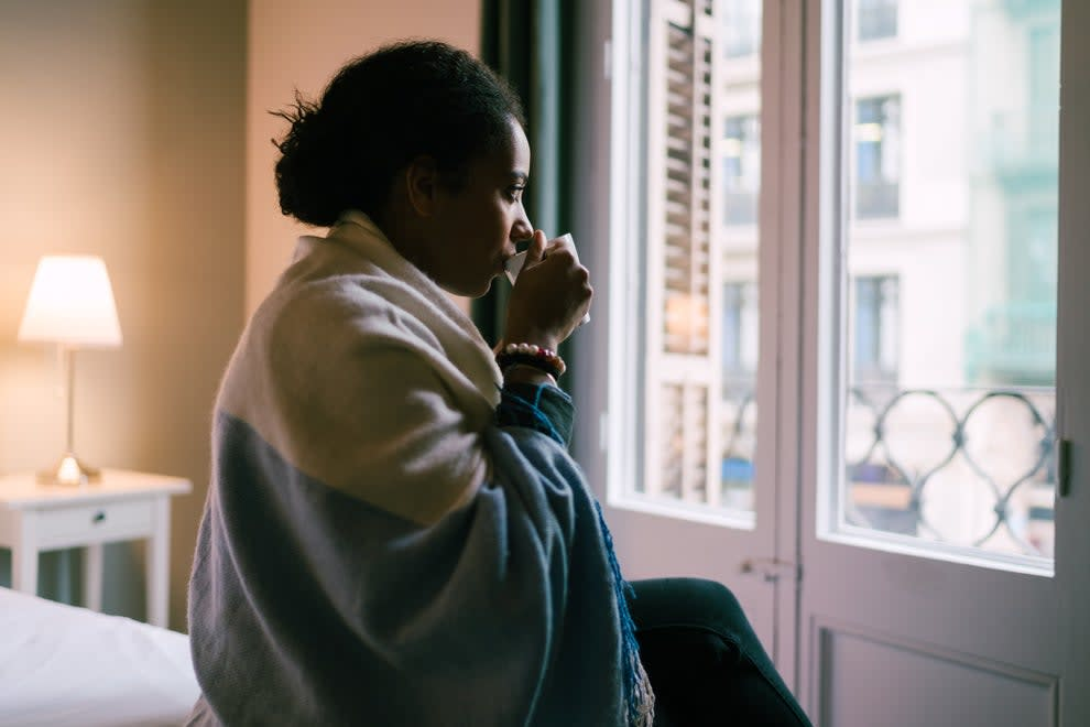 A woman sitting alone inside, looking out a window, as she sips from a mug