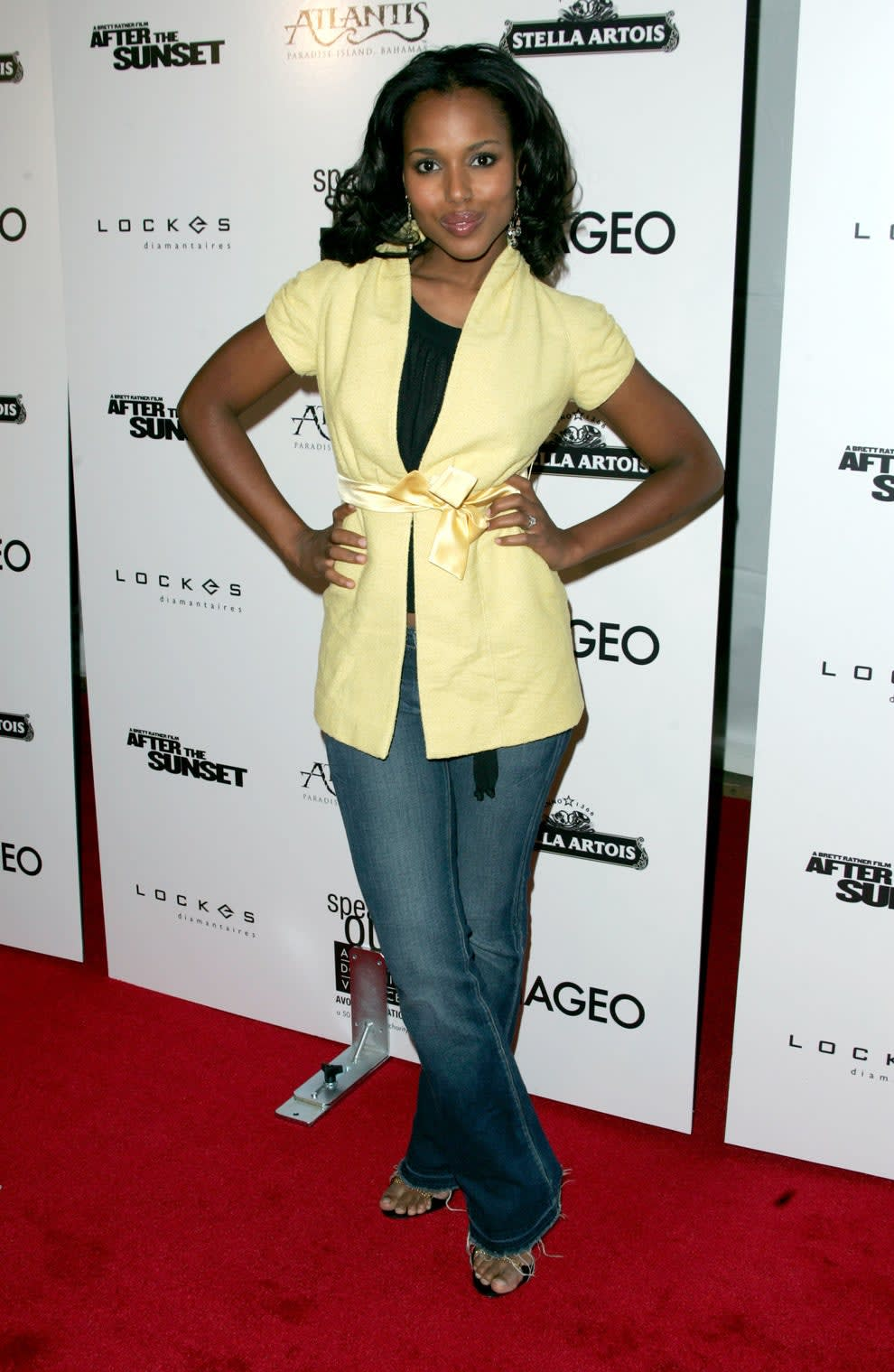 Kerry wears a yellow short-sleeved jacket with a ribbon tied at the waist with dark wash jeans and sandals.