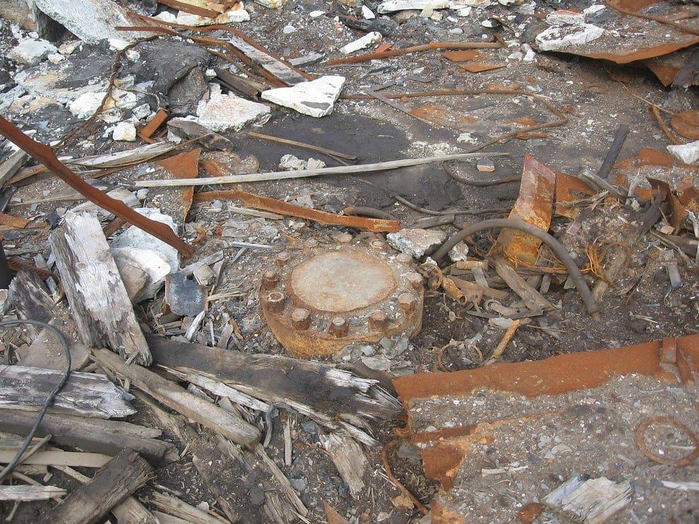 uma tampa fechando o buraco, com sujeira ao redor
