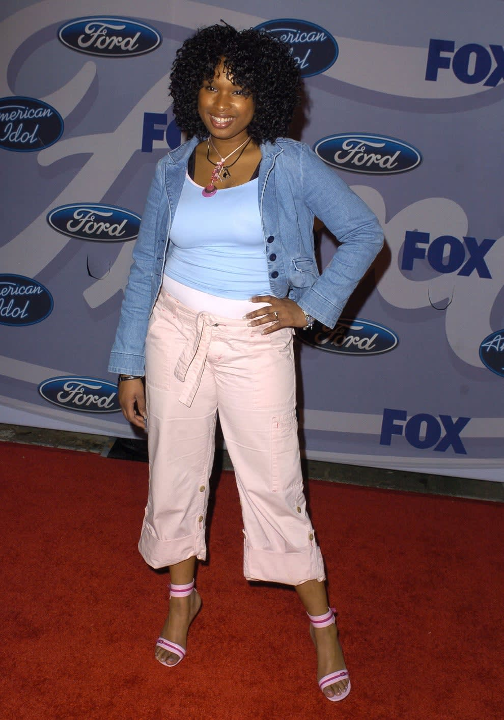 Jennifer wears a t-shirt underneath a denim jacket and khaki capri pants with strappy heels.