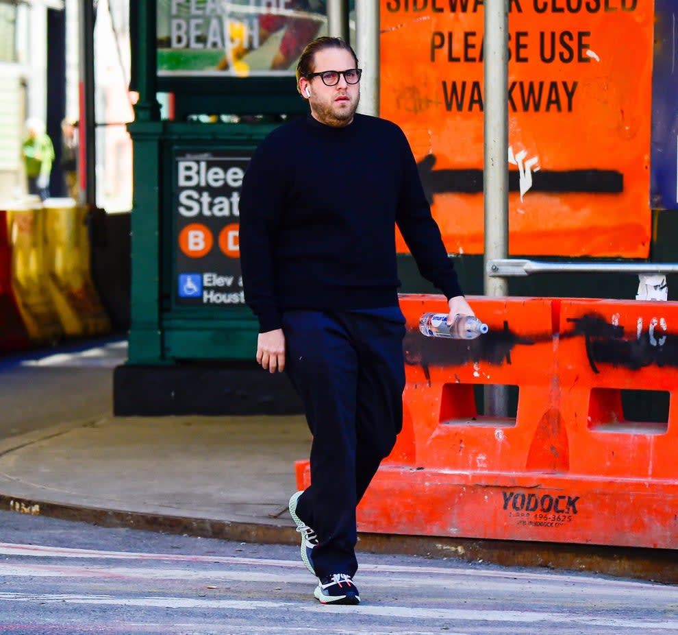 A bespectacled Jonah, wearing sneakers and holding a beverage bottle, walks past the Bleecker Street station in New York City