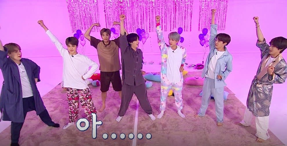 BTS wear pyjamas and have their arms raised on a set decorated with purple streamers and balloons