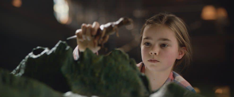 Imagem do filme uma uma criança brinca com um dinossauro de brinquedo.