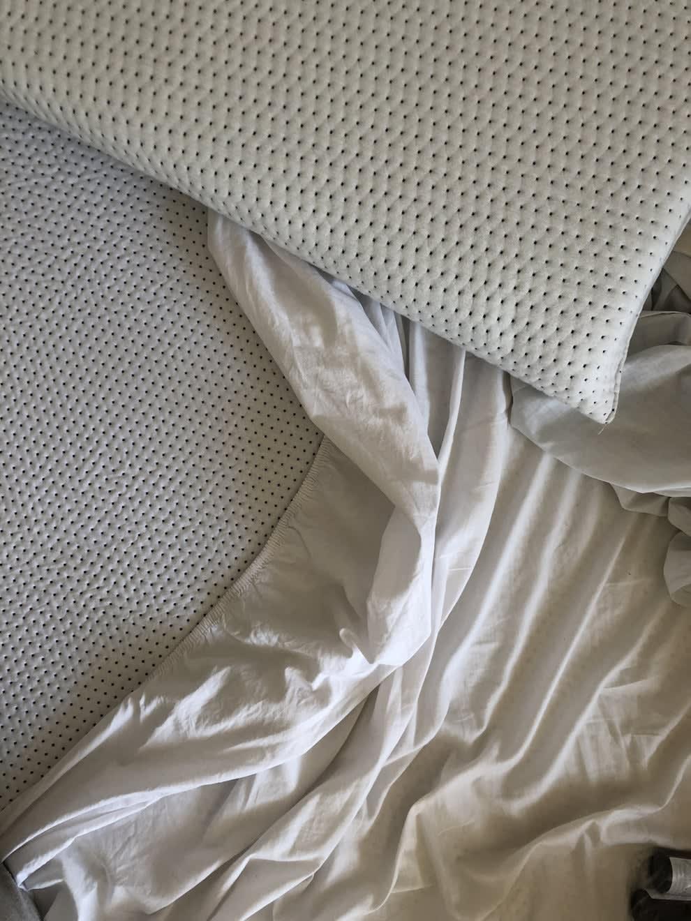Foto do colchão com um pedaço do lençol branco solto. Em cima dele, um travesseiro feito do mesmo material do colchão.