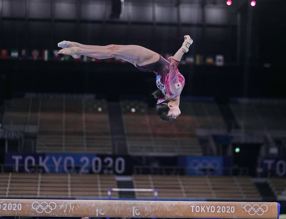 A gymnast doing a flip over the beam