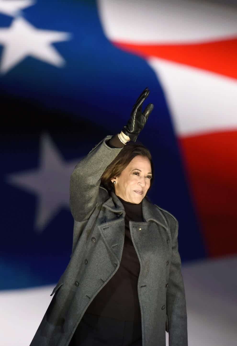 Kamala Harris acenando em frente a uma bandeira dos EUA.