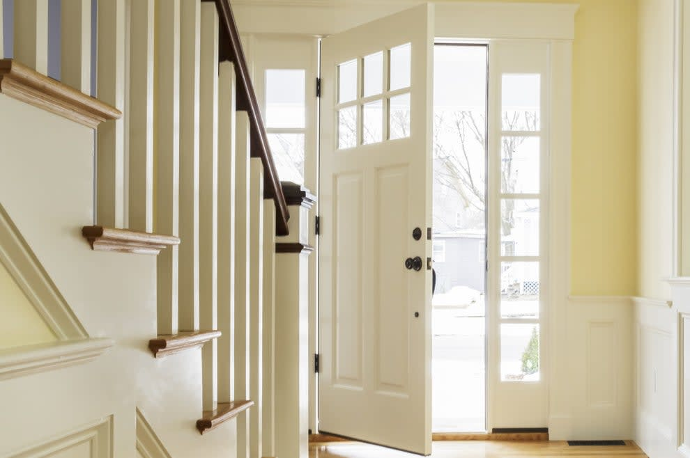The inside of a foyer with the front door open