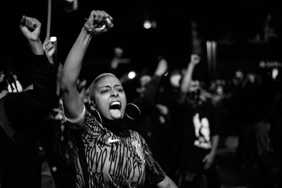 Mulher de raspado vestindo camiseta com estampa de pixo e brincos de argola, com bandana preta no pescoço, gritando com braço erguido.