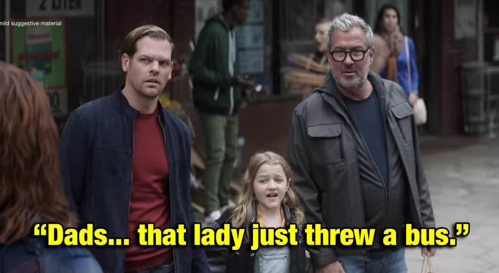 uma garotinha dizendo pros seus pais gays que uma super-heroína arremessou um ônibus inteiro