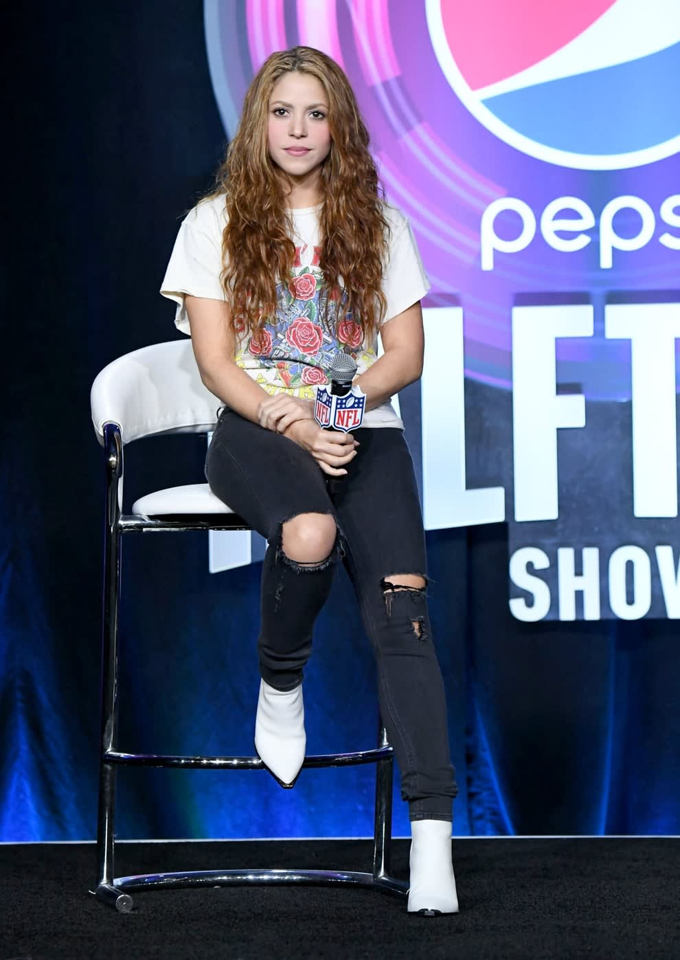 Shakira wears a graphic tee, skinny jeans with holes at the knees, and pointy toed boots.