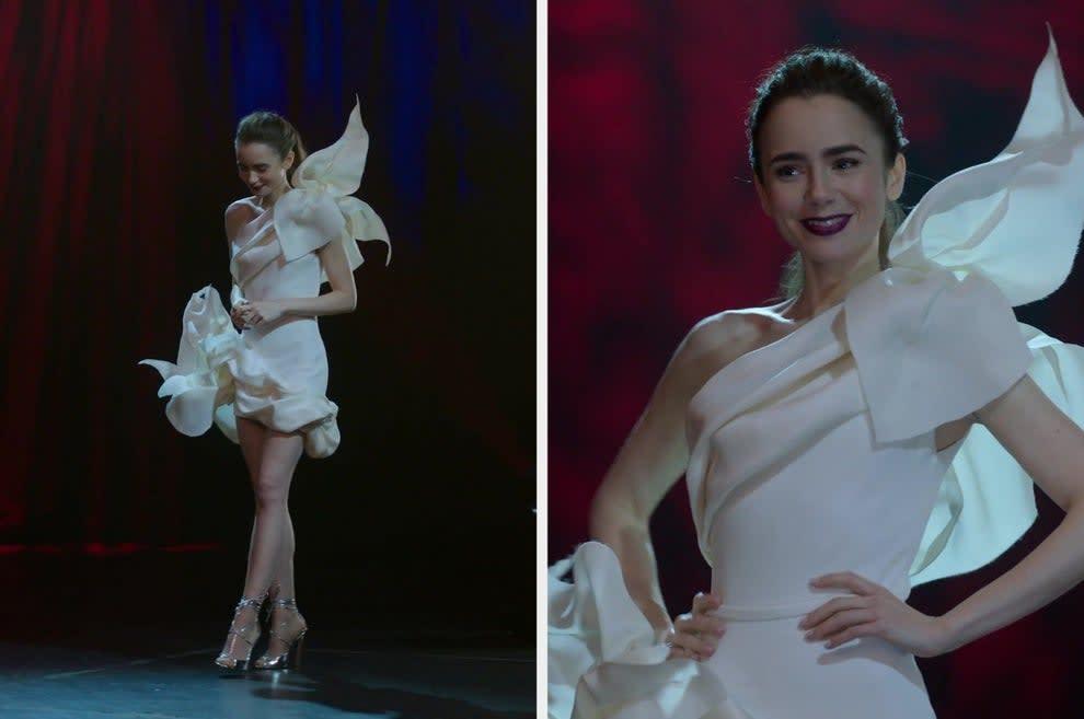 Uma mulher de cabelo preso,  salto alto prata e um vestido branco de alta costura.