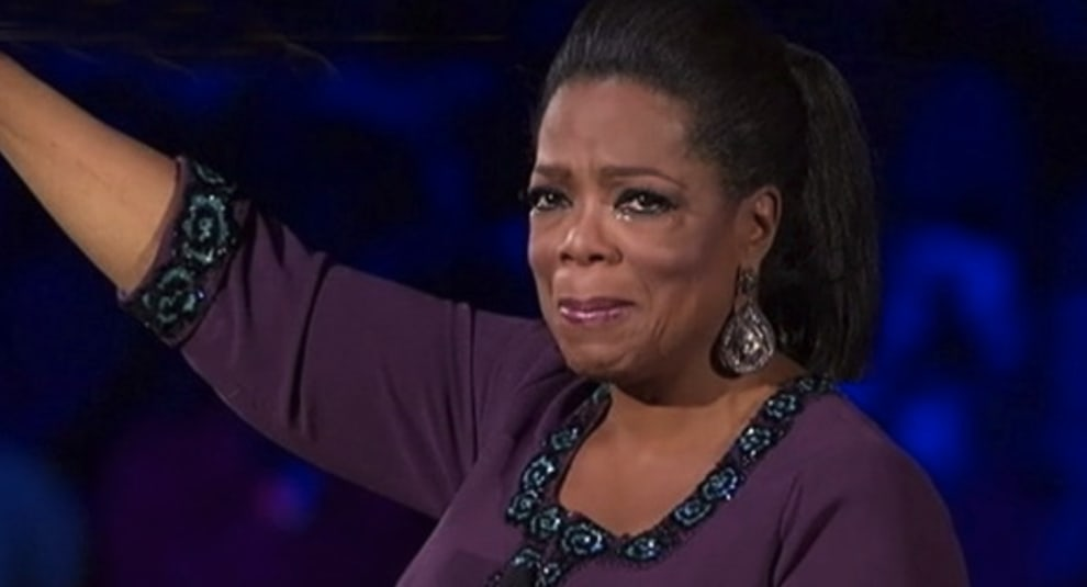 Oprah crying and holding her hand up