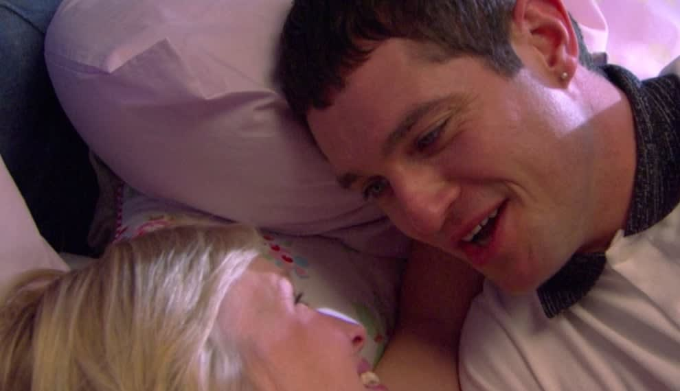 Gavin and Stacey lay on a bed in each other's arms smiling