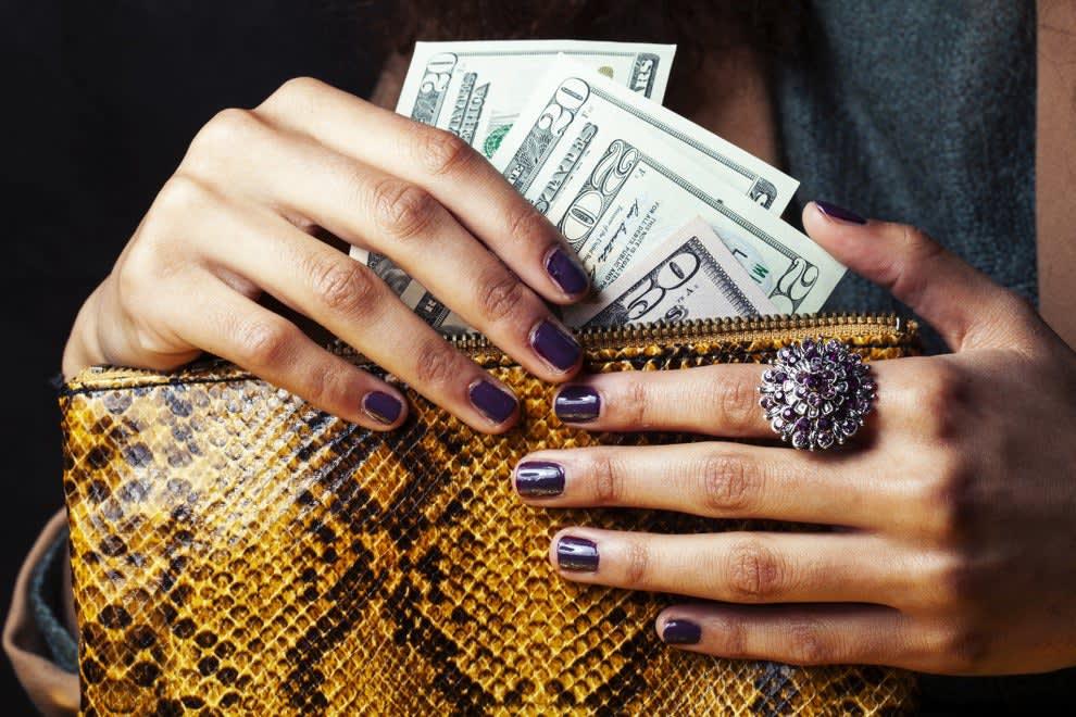 mãos com unhas pintadas e anel tirando notas de 20 e 50 dólares de uma carteira