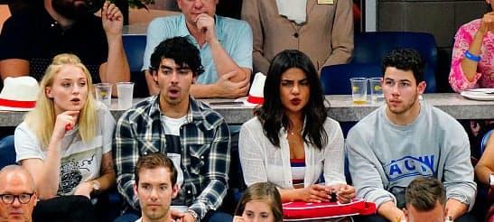 Sophie, Joe, Priyanka, and Nick sitting together and making expressive faces