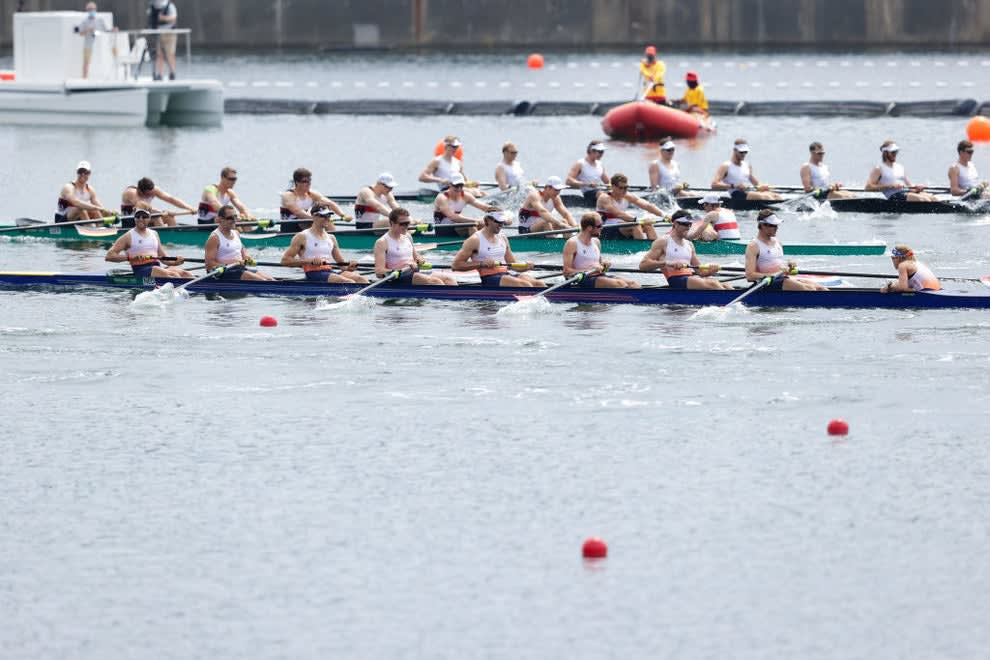 A rowing team with the coxswain sitting on the far right