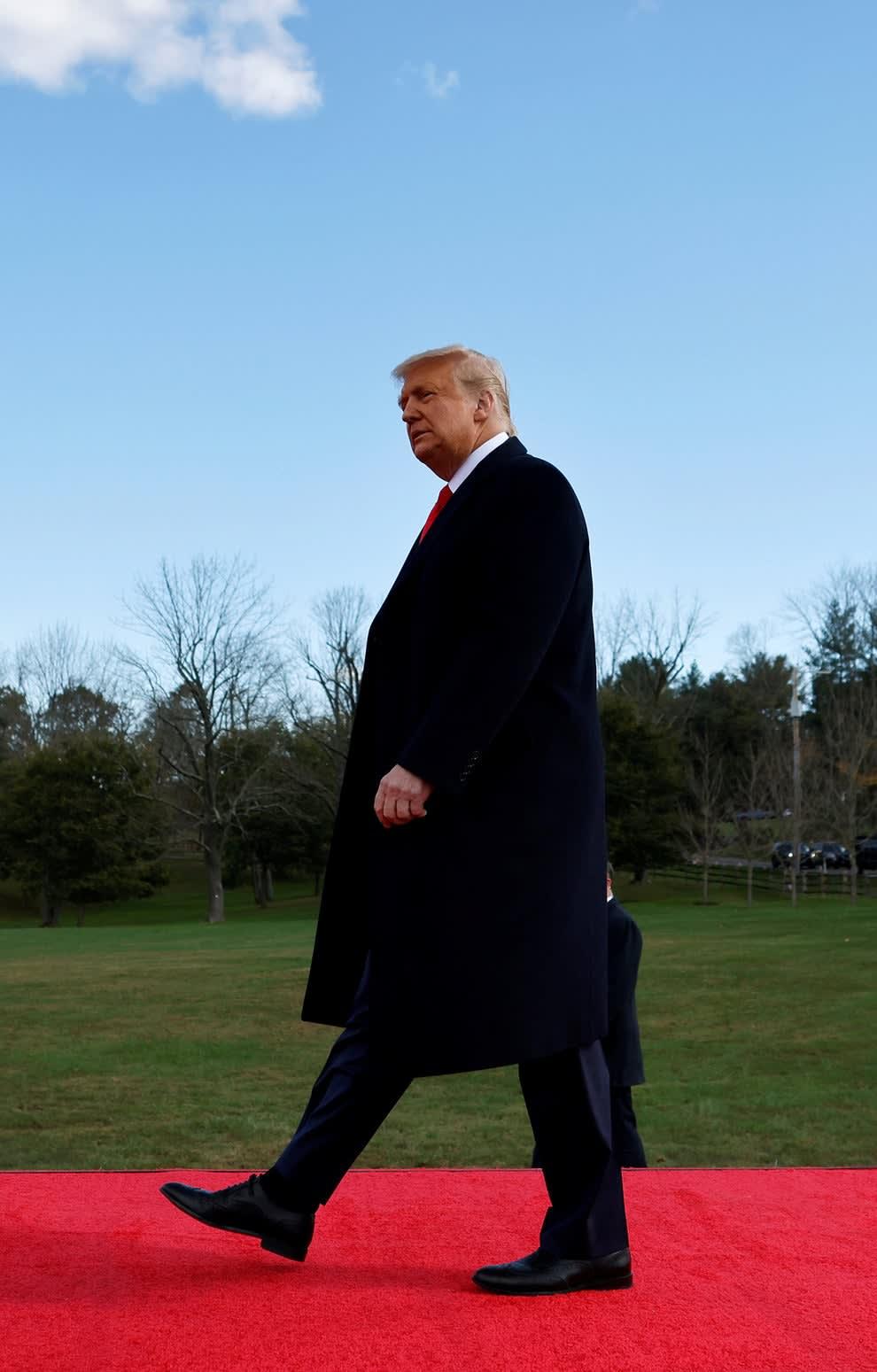 Donald Trump andando em um tapete vermelho sobre um gramado..