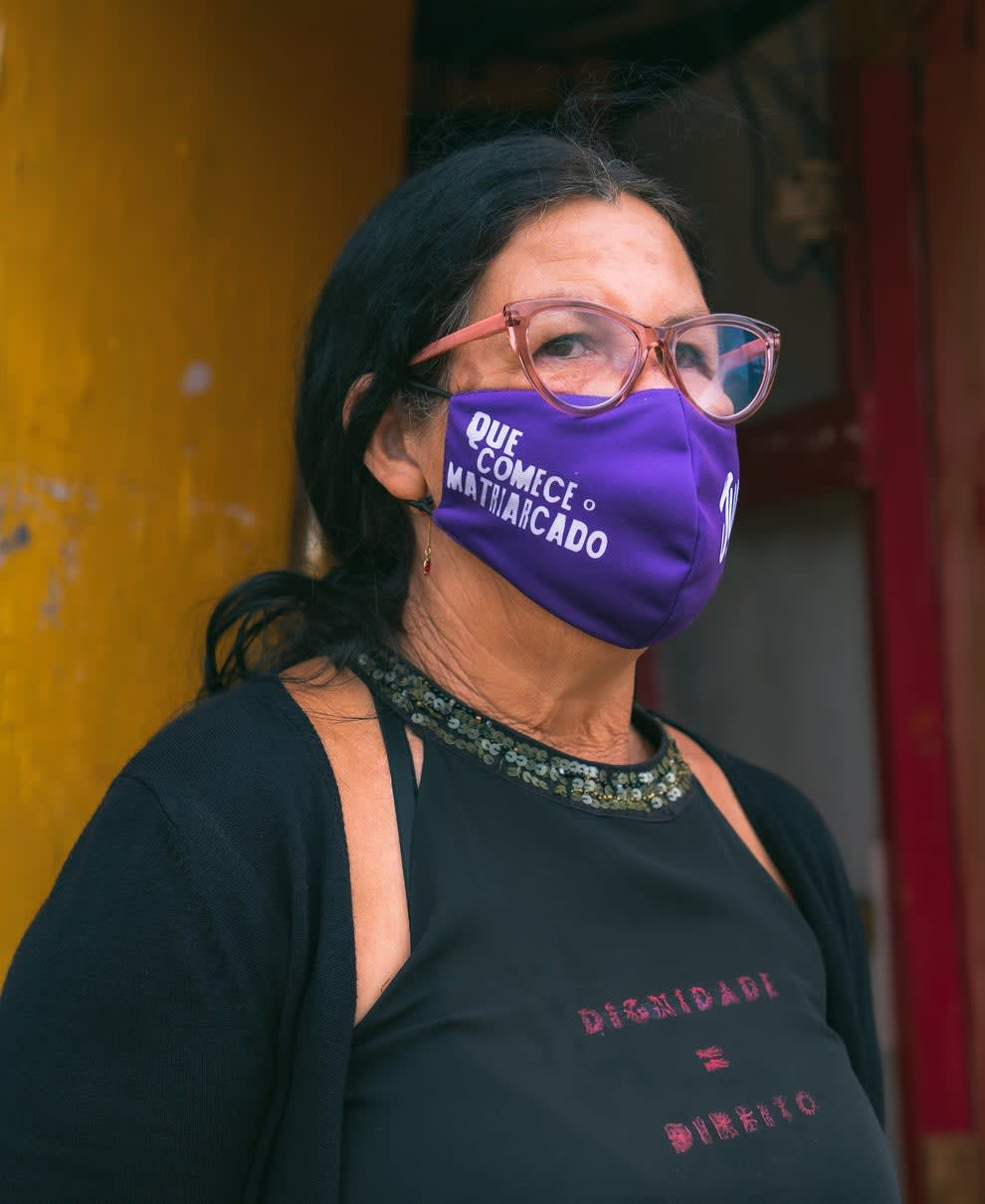 Dona Cigana, moradora da ocupação, vestindo uma camiseta preta onde se lê Dignidade = Direito e uma máscara rosa escrito Que Comece o Matriarcado.