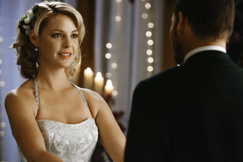 Heigl wears a wedding dress and holds a man's hands while looking into his eyes