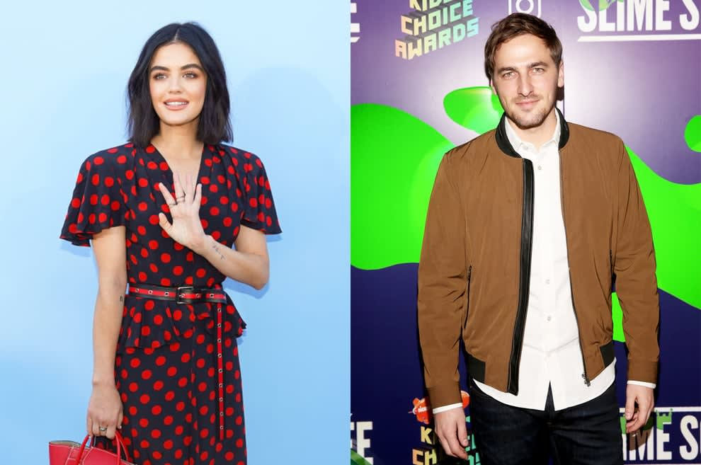 Lucy, holding a tote bag, smiles and waves, while Kendall in a jacket smiles on the Kids' Choice Awards red carpet