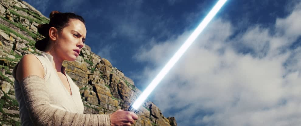 """Daisy Ridley holding a lightsaber in """"Star Wars: The Last Jedi"""""""
