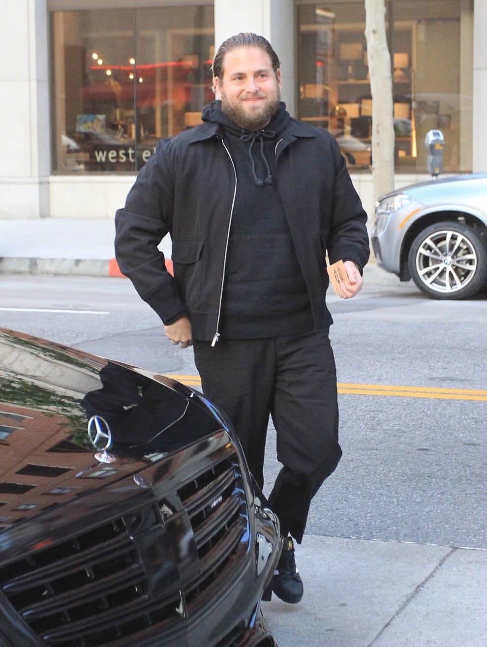 Jonah smiles as he walks by a car