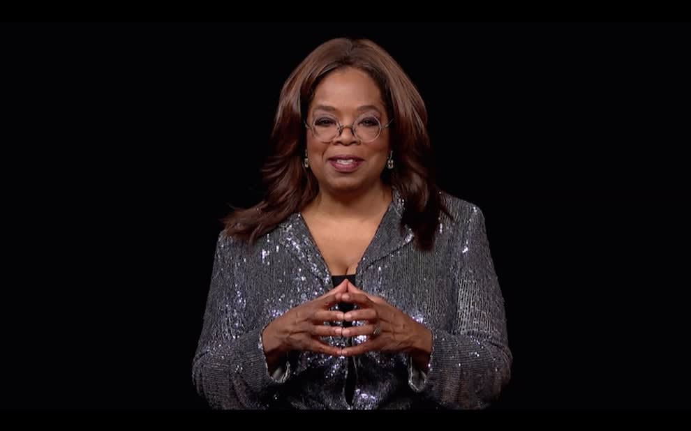 Oprah addresses a camera with her fingertips touching
