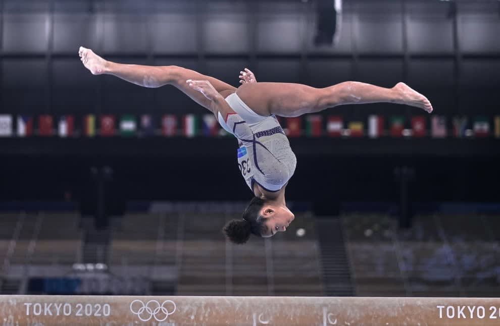 A gymnast airborne and upside down doing the splits over the balance beam