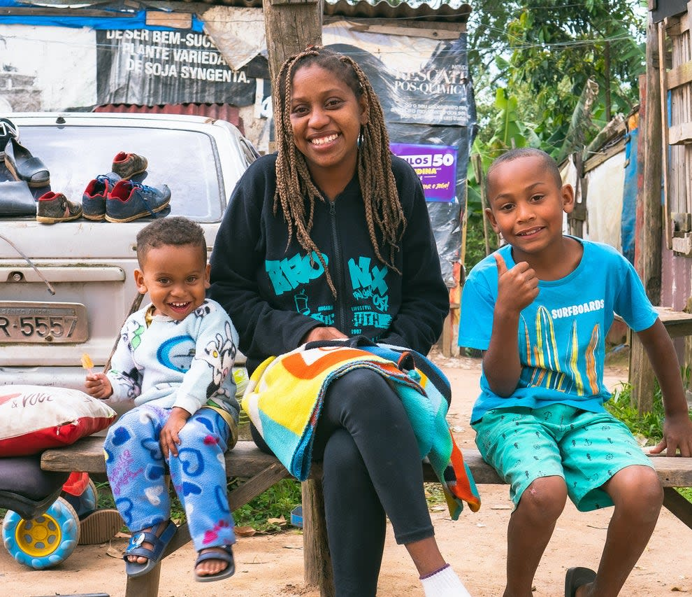 Jovem mulher negra usando tranças e vestindo moletom preto sentada em um banco ao lado de duas crianças que fazem sinal de positivo com as mãos.