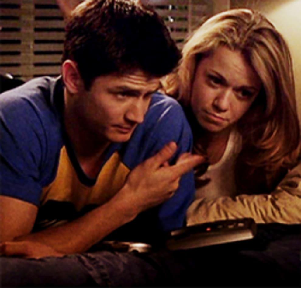 Nathan e Haley com o telefone na cama, eles gravam juntos o novo recado da secretária eletrônica.