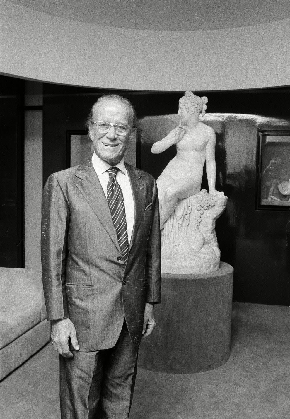 Aldo Gucci standing in front a statue