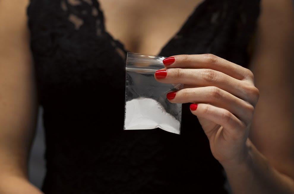 mulher segurando plástico com cocaína