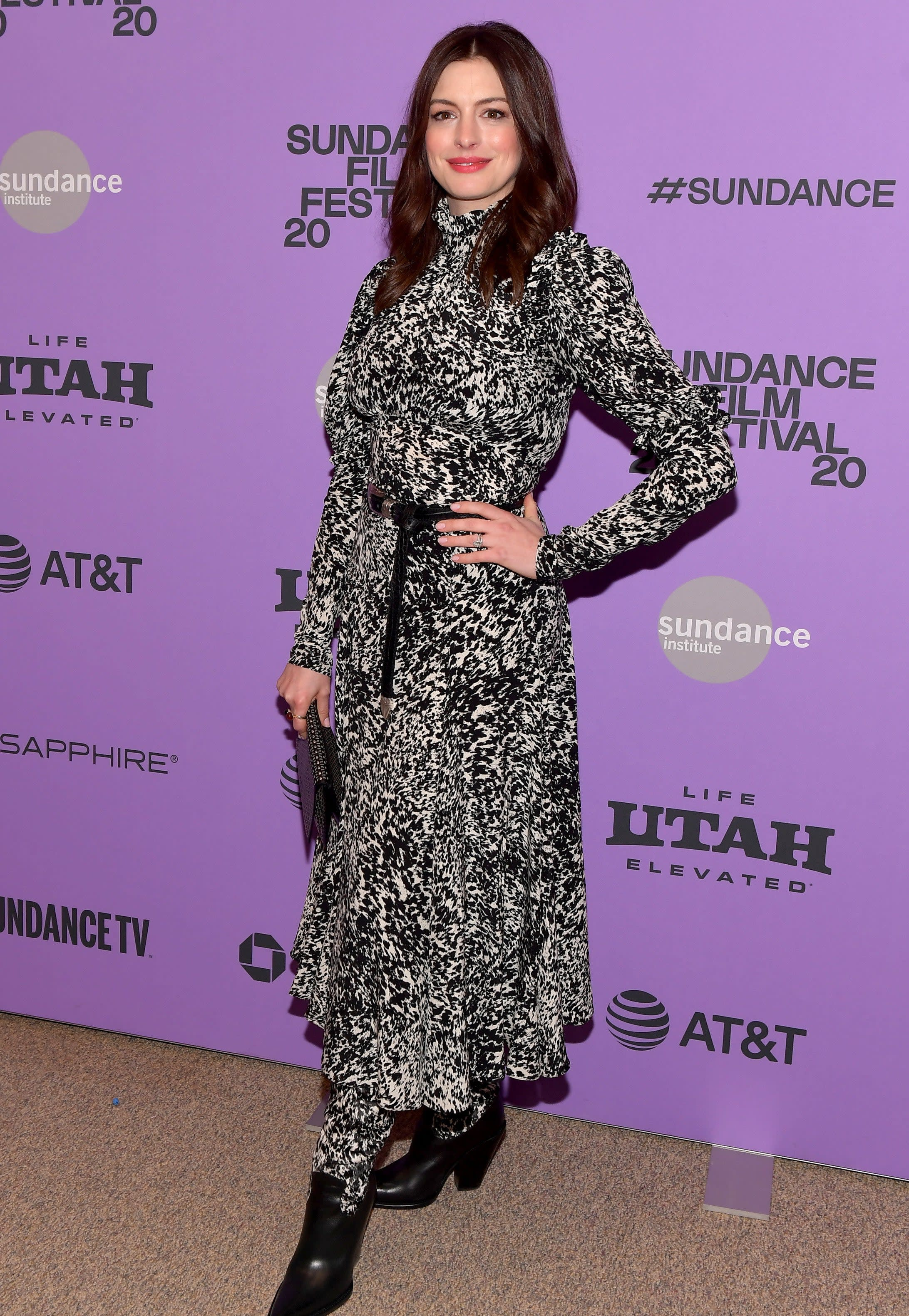 Anne wears a patterned long sleeve dress with booties and a belt at her waist.