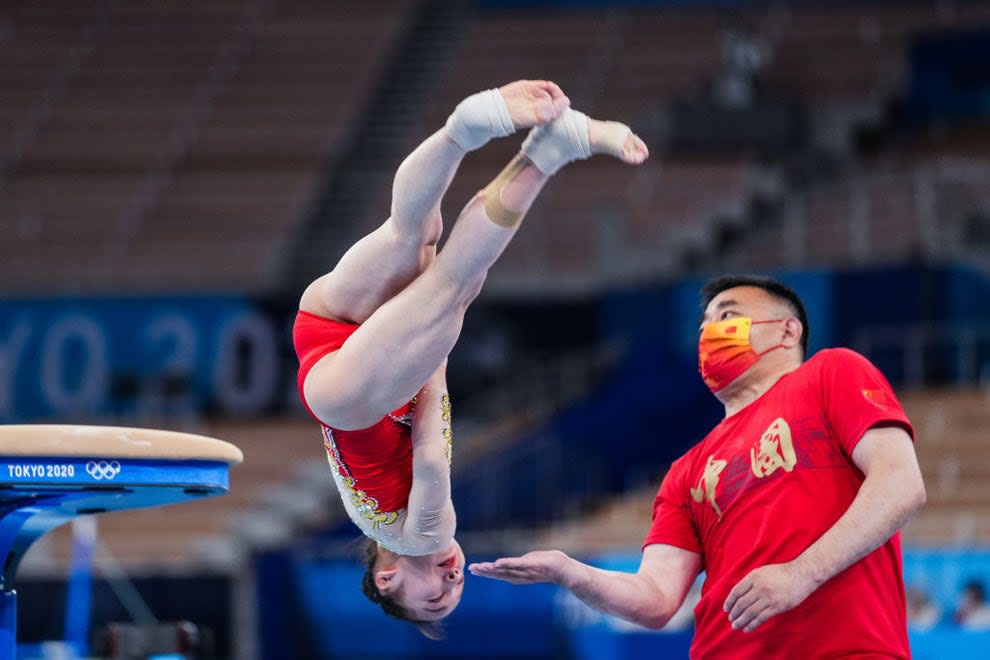 A man with his palm extended as a gymnast attempts to land
