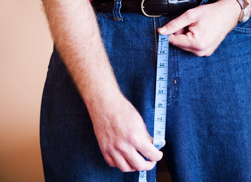 pessoa medindo parte da frente da calça jeans