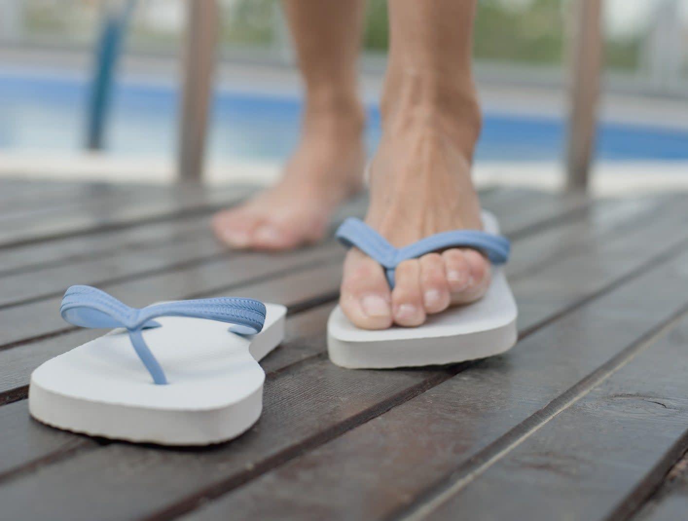 uma pessoa saindo da piscina e colocando um chinelo