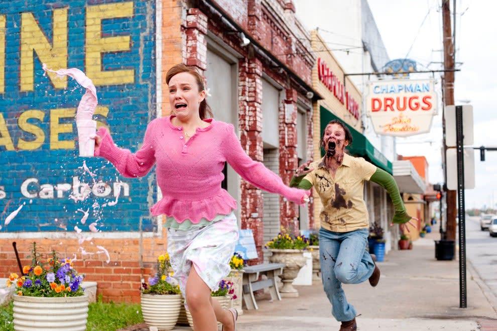 A zombie chasing a dolled up woman running with a smoothie