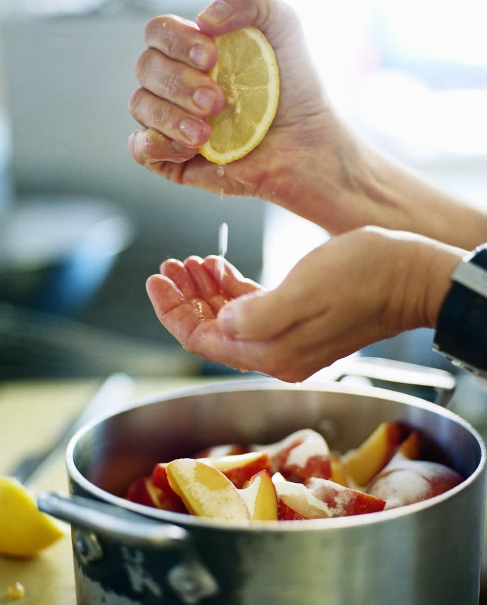 Someone squeezing a lemon into a pot of peaches.