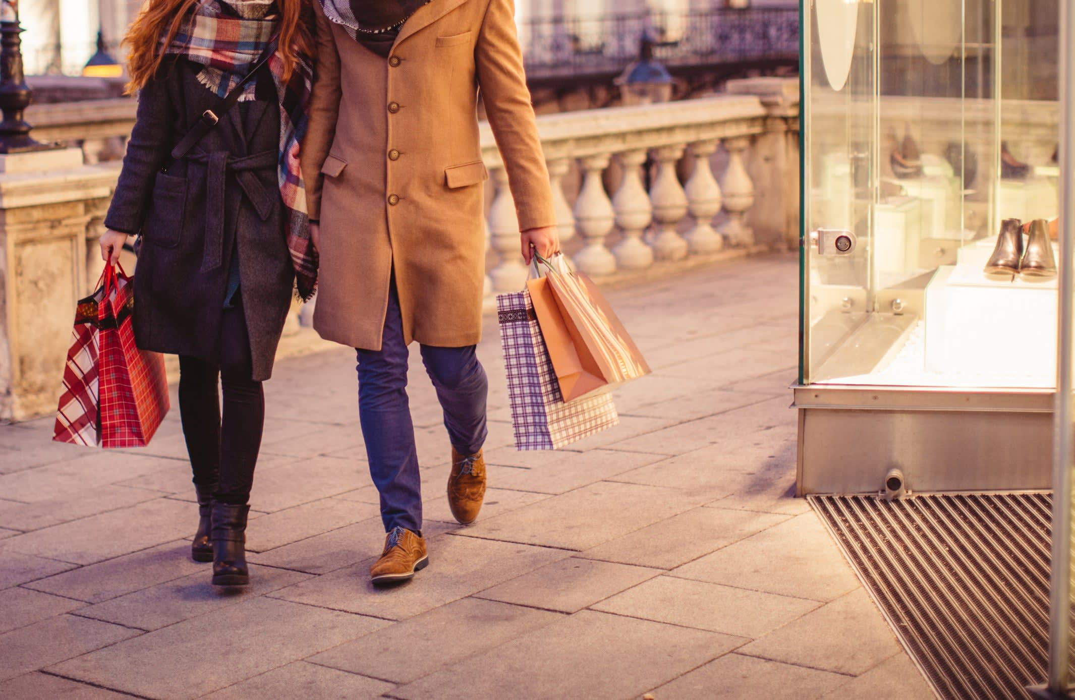 A couple holding shopping bags as they walk past a store