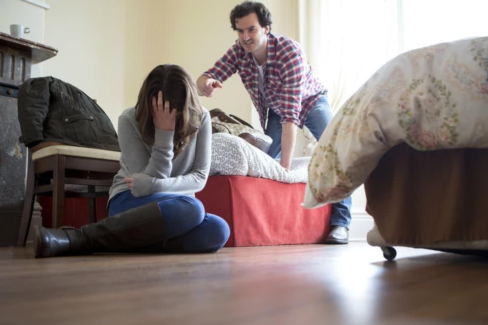 homem apontando dedo para mulher sentada no chão