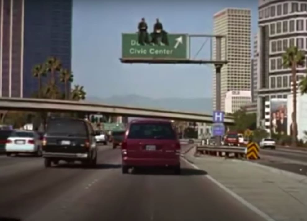 "Nicolas Cage and Andre Braugher sitting on a road sign in ""City of Angels"""