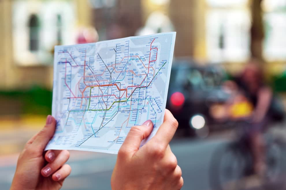 a person's hands holding up the map for the London tube routes