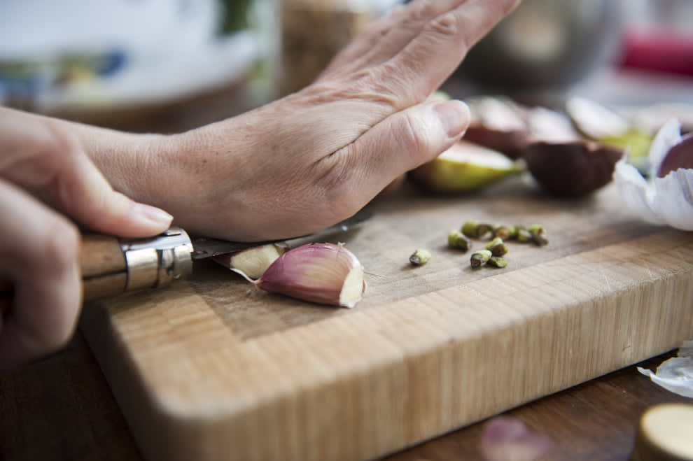 Peeling garlic on a cutting board.