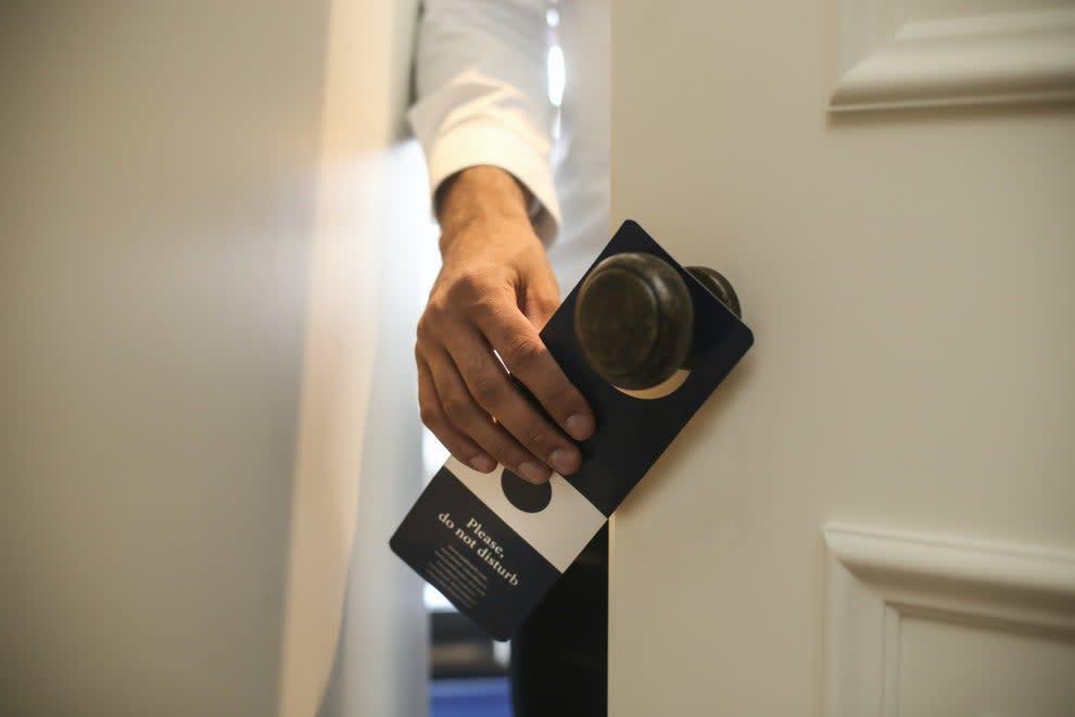 """mão segurando placa de """"não perturbe"""" em porta de hotel"""