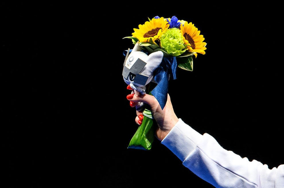 Silver medalist Inna Deriglazova of Team ROC poses with flowers in her hand on the podium