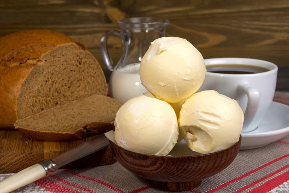 foto de uma mesa de café da manhã com um pão, manteiga, uma xícara de café e um jarro de leite