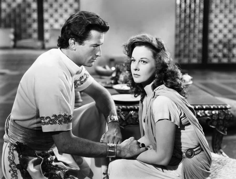 Gregory Peck kneeling down next to Susan Hayward
