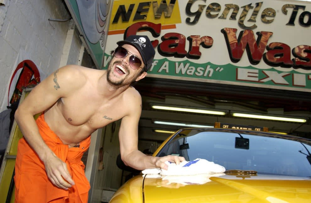 A younger shirtless Johnny waxing down a car